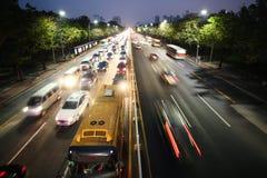 喧闹的大高速公路 沥青汽车阻塞无缝的业务量向量墙纸 夜生活和城市光的 免版税库存图片