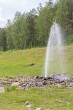 喷出从在河的河岸的地面的自然喷泉 图库摄影