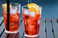 喷开胃酒与两个橙色切片和冰块的aperol鸡尾酒 免版税库存照片