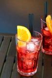 喷开胃酒与橙色切片和冰块的aperol鸡尾酒在颜色梯度背景 库存照片