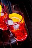 喷开胃酒与橙色切片和冰块的aperol鸡尾酒在颜色迪斯科光背景 免版税库存照片