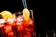 喷开胃酒与橙色切片和冰块的aperol鸡尾酒在黑色 免版税图库摄影