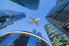 喷气式客机飞机在摩天大楼上飞行 图库摄影