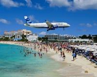 喷气机到圣马丁里飞行非常低在海滩 免版税库存照片