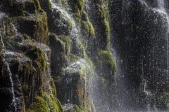 水喷气机和滴反对黑岩石的 免版税库存图片