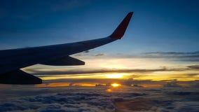 喷气机在云彩的` s翼剪影在高处,当日落 免版税库存图片