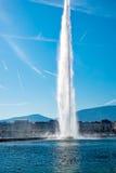 喷气机在莱芒湖的d'eau (水喷气机)喷泉有城市的在背景和飞机中在天空落后 图库摄影