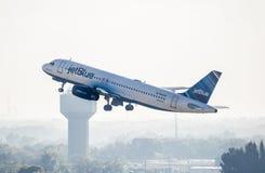 喷气机蓝色有雾的天起飞 免版税库存图片