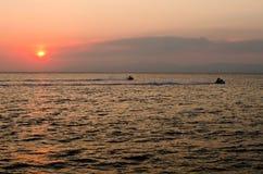 喷气机滑雪在日落的海 免版税库存照片