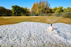 喷水的注射器和冰在草坪 免版税库存图片