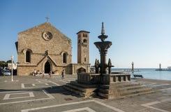喷泉和Evangelismos教会在Mandraki港口,罗得岛, G 免版税库存照片
