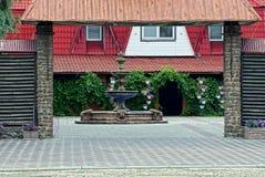 喷泉在房子附近的一个私有庭院里在一个开放门后 免版税图库摄影