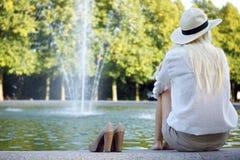 喷泉坐的等待的妇女 免版税图库摄影