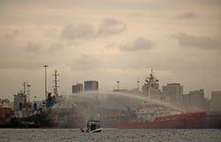 喷洒从巡逻舰的甲板的水在港口 库存图片