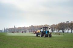 喷洒农业化肥或agrichemical结束y的麦田拖拉机 免版税库存图片