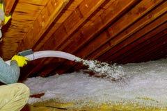 喷洒吹的玻璃纤维绝缘材料的技术员在顶楼之间捆绑泡沫绝缘材料从枪的建筑泡沫到屋顶 库存图片
