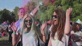 喷洒在俏丽的女孩的人五颜六色的粉末,愉快的朋友停留在事件 股票视频