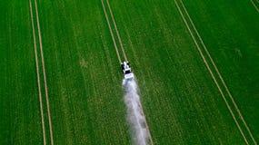 喷洒在大绿色领域的拖拉机的鸟瞰图化学制品 库存照片