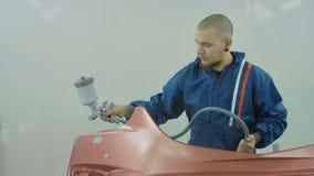 喷洒在汽车前保险杆的自动画家红色油漆在特别摊 免版税库存照片