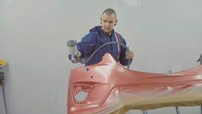 喷洒在汽车前保险杆的自动画家红色油漆在特别摊 库存照片