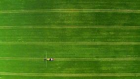 喷洒在绿色领域,鸟瞰图的小拖拉机化学制品 影视素材