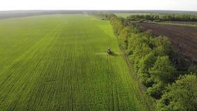 喷洒在领域的农用拖拉机鸟瞰图与喷雾器、除草药和杀虫剂在日落 农业机械 股票视频
