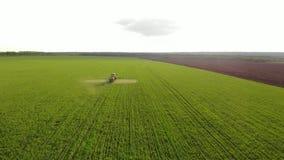 喷洒在领域的农用拖拉机鸟瞰图与喷雾器、除草药和杀虫剂在日落 农业机械 影视素材