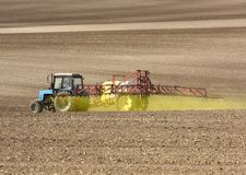 喷洒在领域的拖拉机化学制品 拖拉机洒 库存图片