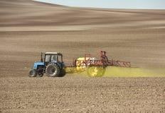 喷洒在领域的拖拉机化学制品 拖拉机洒 免版税库存图片