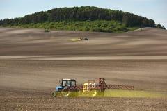 喷洒在领域的拖拉机化学制品 拖拉机洒 库存照片
