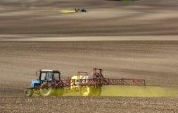 喷洒在领域的拖拉机化学制品 拖拉机洒 免版税库存照片