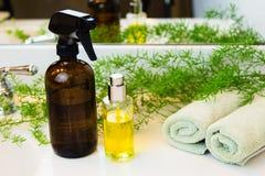 喷洒瓶、毛巾和绿色在卫生间工作台面 免版税库存照片