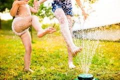 喷水隆头的,晴朗的夏天两个女孩在庭院里 免版税库存照片