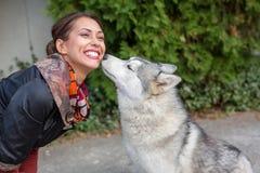 嗅一名美丽的妇女的逗人喜爱的幼小多壳的狗 免版税库存照片