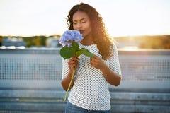 嗅到一朵俏丽的花的黑人妇女 图库摄影