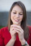 嗅到一朵小的雏菊的妇女 免版税库存照片