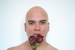 嗅到一朵红色玫瑰的人 免版税图库摄影