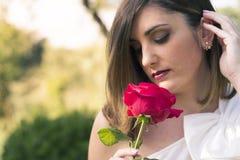 嗅到一朵红色玫瑰的可爱的妇女 免版税库存图片