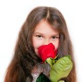 嗅到一朵红色玫瑰的小女孩 免版税库存图片