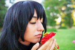 嗅到一朵红色花的少妇 免版税图库摄影