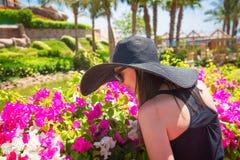 嗅到一朵花的妇女在公园 免版税库存图片