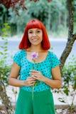 嗅到一朵花的红头发人妇女在公园 免版税库存照片