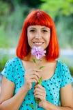 嗅到一朵花的红头发人妇女在公园 图库摄影
