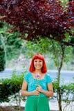 嗅到一朵花的红头发人妇女在公园 免版税库存图片