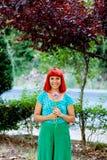 嗅到一朵花的红头发人妇女在公园 免版税图库摄影