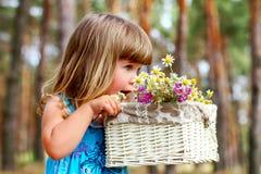 嗅到一朵雏菊的小女孩在夏天森林里 库存图片