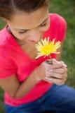 嗅到一朵黄色花的妇女 库存图片