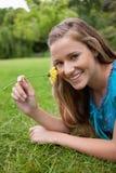 嗅到一朵黄色花的微笑的女孩,当位于时 免版税库存图片