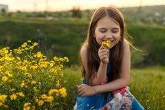 嗅到一朵黄色花的小女孩 图库摄影