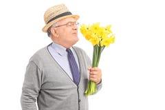 嗅到一束黄色郁金香的资深绅士 库存照片